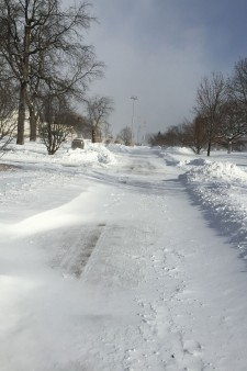 Photo of an empty campus sidewalk being covered over by drifting snow.