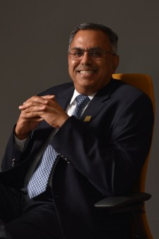 Dean Satish Deshpande, sitting in a chair, smiling