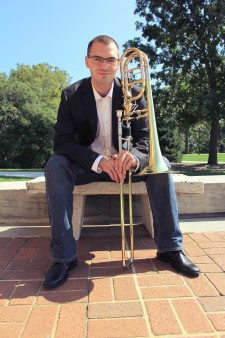 Evan Clifton sitting on a patio holding a bass trombone.