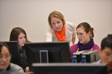 a photo of a faculty memeber looking over the sholders of two student who are seated at computers in a computer lab. She is pointing at a computer monitor and explainging something as the two seated women watch and listen.