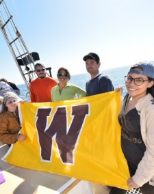 Fish biology students aboard the Inland Seas Education Association schooner holding a W flag.