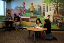 students at tables in front of a mural