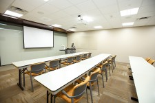 rows of tables and chairs facing a projector screen and rolling podium workstation in a wmu-grand rapids, beltline room.
