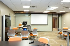 active learning room at wmu-grand rapids, beltline. computer chairs around multiple desks and wall-mounted monitors. rolling podium workstation in front of room next to projector screen.