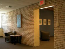 a chair and small table in front of a brick wall and some decor in a wmu-grand rapids, downtown room.