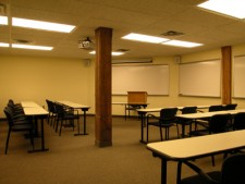 a wmu-grand rapids, downtown room. five rows of tables and chairs angled and facing a podium and two whiteboards at the front of the room.