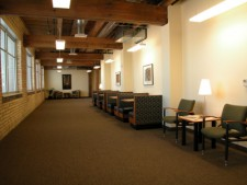 a wmu-grand rapids, downtown hallway lined with chairs, small tables, and windows.