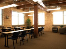 a large open space in wmu-grand rapids, downtown with chairs and tables arranged in a 'u' shape.