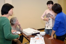 Photo of an instructor pointing to an example of Chinese painting.