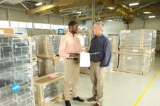 Photo of an ISM student in a warehouse with a client.