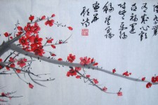 Photo of an ink painting that features a tree branch with red blossoms below Chinese writing.