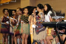 Photo of musical performers with geometric designs painted on their faces and arms and dressed in grass skirts.