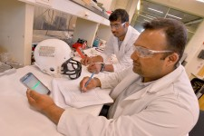 Photo of two people in white lab coats conducting a test on the Massood team's impact-sensing system, with one of the people writing down the data being collected.