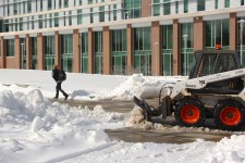 Photo of a small bulldozer scraping snow from the sidewalk in front of Sangren Hall.
