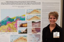 Photo of VanderMeer posing with a huge poster that describes her research through text as well as colorful drawings and photos.