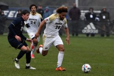 WMU men's soccer player No. 26 Jay McIntosh kicks the ball as an Akron player approaches.