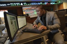 Photo of a male WMU student examining dual computer screens inside WMU's Greenleaf Trust Trading Room.