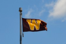 A brown and gold W flag flies at full-staff.
