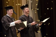 Two male students in graduation caps and gowns use their diploma folders to catch some of the confetti being dropped during their commencement ceremony.