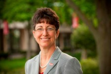 Photo of Dr. Terri Goss Kinzy standing outside with trees in the background.