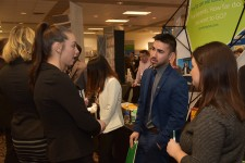 Photo of a male and female student discussing their job prospects at a booth during the 2017 winter Career Fair.