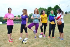 A group of women poses with athletic equipment, including a soccer ball, badminton racket and basketball.