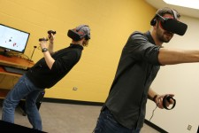 Two people wearing virtual reality goggles and holding controllers near a computer screen.