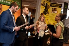 Photo of three WMU students speaking with a recruiter at a career fair.