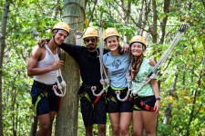 WMU WeSustain interns are shown during a retreat activity in ziplining gear in front of trees.