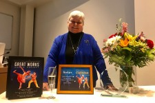 WMU emerita Wendy Cornish standing at a table with Great Works awards and displays.