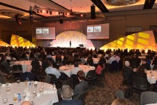 Wide photo of past conference attendees sitting at tables listening to a speaker..