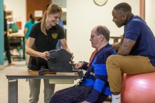Two WMU students help an older man complete occupational therapy exercises.
