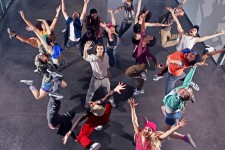 Aerial shot of a stage full of WMU student actors with their arms stretched upward.