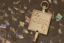 Phi Beta Kappa golden key on a background of graduation caps.