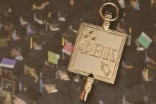 Phi Beta Kappa golden key on a background of graduation caps.