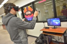 A student wears virtual reality goggles and holds up two controllers while watching a nearby computer screen.