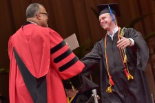 A grinning male student embraces President Montgomery while receiving his diploma.