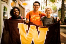 "Three students hold a brown and gold ""W"" flag while standing outside in downtown Kalamazoo."