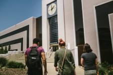 Three WMU students walk up to Waldo Library's main entrance.