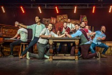 Photo of a group of male performers leaning over a table on a stage with a man playing a piano in the backgroud.