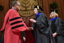 A newly hooded doctoral student accepting her diploma from WMU President Edward Montgomery.