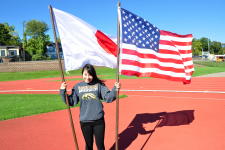 Japanese exchange student in WMU sweatshirt smiles while holding a Japanese flag and a U.S. American flag.