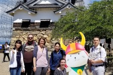 Joshua White and other language students posing with the mascot of Hikone at Hikone Castle.