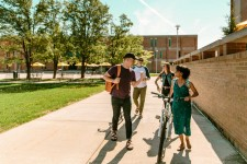 Group of students walking and riding bicycles on WMU's main Kalamazoo campus.