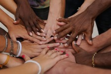 Hands from numerous diverse individuals overlapping one another.