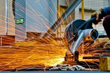 Worker using a saw to cut through metal. Sparks fly in the foreground.