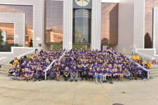 A large group of Fall Welcome student ambassadors sitting on steps in front of a building.