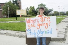 A student holding a handwritten sign promoting the Study Abroad Fair.