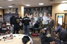 WMU football team members interacting with passport facility staff.