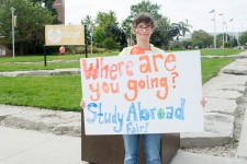 Student holding a Study Abroad Fair sign.